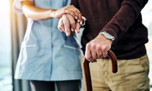 Shot of a young nurse assisting a senior man who's walking with a cane