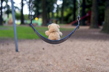 Teddybear sitting alone on a swing set at the park