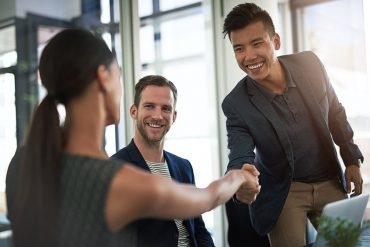 Shot of businesspeople shaking hands in an office