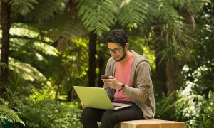 Young man with a laptop and smartphone sitting outdoor in a park