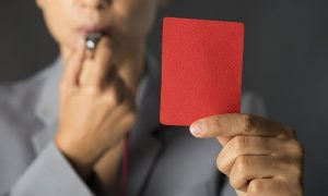 Business woman holding red card and blowing a whistle