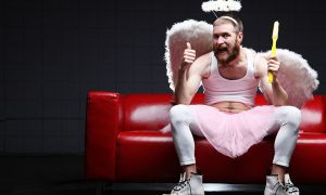 Humorous male tooth fairy holding a giant toothbrush and showing a thumbs up. Dark background and sitting on a red couch.
