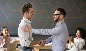 Team leader handshaking employee congratulating with professional achievement or career promotion, thanking for good project result while team supporting applauding, appreciation recognition concept