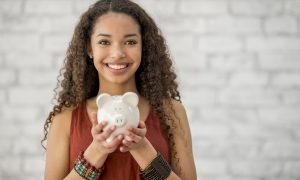 A teenage girl with long curly hair is indoors. She is smiling at the camera while holding a piggy bank. She is saving money for a big purchase.